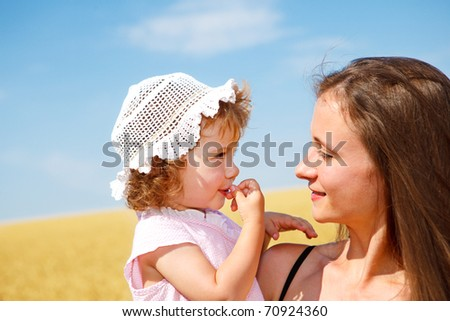 Portrait of woman and curly toddler girl in the outdoor