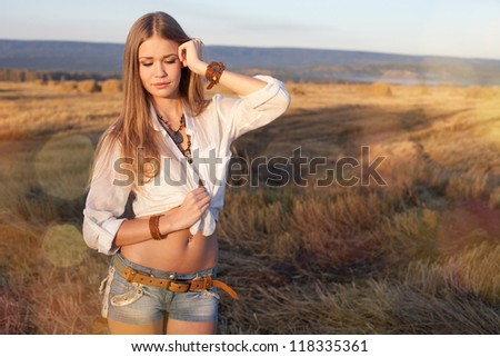 Portrait of woman at the field. Young woman in costume of cowboy sideways.
