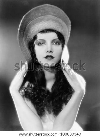 Portrait of woman bending edges of hat