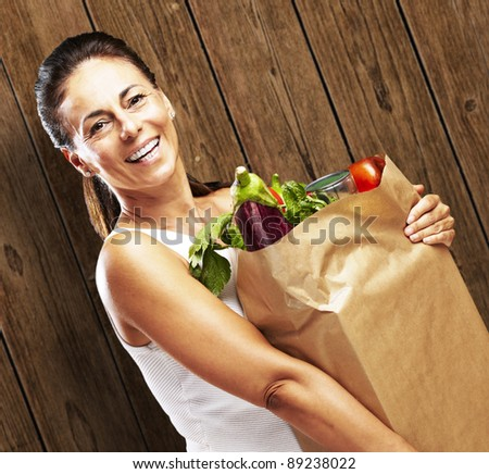portrait of woman carrying food against a wooden wall