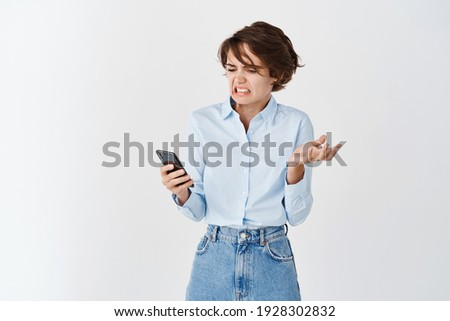 Portrait of woman cringe and look with disgust at mobile screen, reading something disgusting, stare with aversion, white background. Foto stock ©