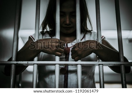 Portrait of woman desperate to catch the iron prison,prisoner concept,thailand people,Hope to be free.