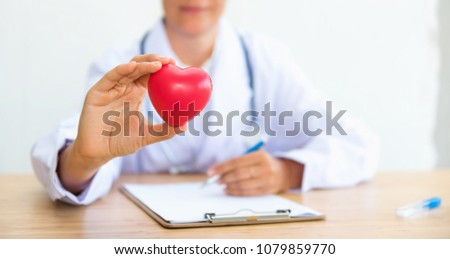 Portrait of woman doctor with holding red heart., Healthcare and occupation concept. #1079859770
