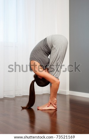 portrait of woman doing flexibility exercise in room