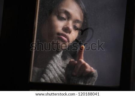 Portrait of woman drawing heart on wet window - stock photo