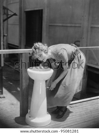 Portrait of woman drinking from water fountain