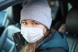 Portrait of woman driver wearing facemask in car, winter season, female dressing hat and coat