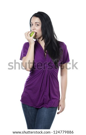 Portrait of woman eating green apple against white background