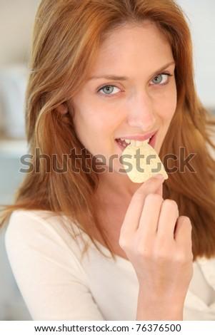Portrait of woman eating potato chip #76376500