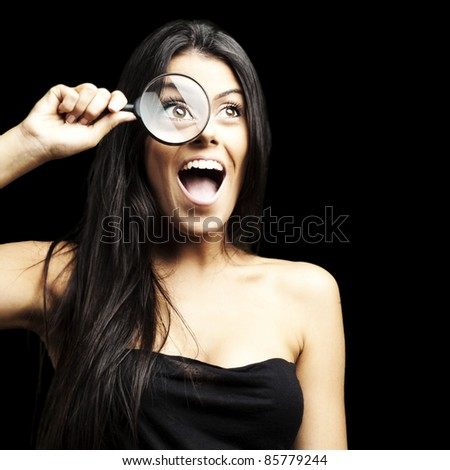 portrait of woman excited looking through a magnifying glass over black background