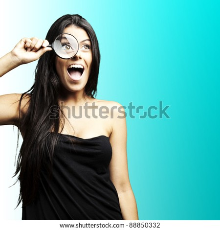 portrait of woman excited looking through a magnifying glass over blue background