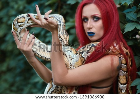 Portrait of woman holding and showing spooky big snake on hand. Model with red hair, red brows and blue lips looking at camera, posing outdoors near bushes.