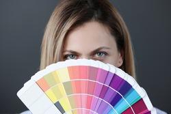 Portrait of woman holding fan of color palette. Selection by stylist of the color scheme concept