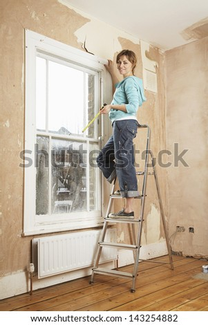 Portrait of woman holding measure tape while standing on step ladder in unrenovated house