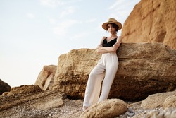 Portrait of woman in black bralette and white trousers leaning on rock at beach