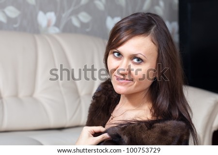 Portrait of woman  in fur coat  at home interior