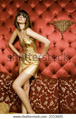 Portrait of woman in gold dress in interior