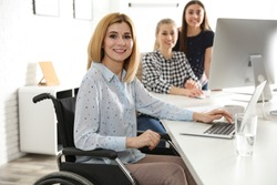 Portrait of woman in wheelchair with her colleagues at workplace