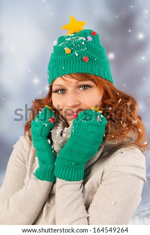Portrait of woman in winter with snow and hat and gloves of Christmas tree