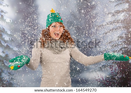 Portrait of woman in winter with snow and hat and gloves of Christmas tree and lots of fun in snowstorm