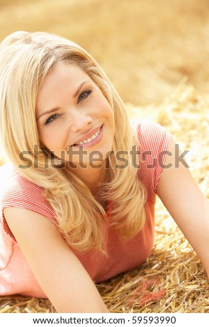 Portrait Of Woman Laying In Summer Harvested Field