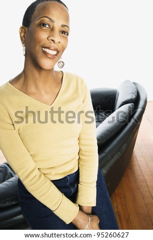 Portrait of woman leaning on couch