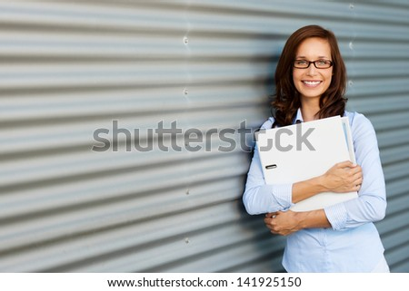 Portrait of woman leaning on the wall and holding a laptop