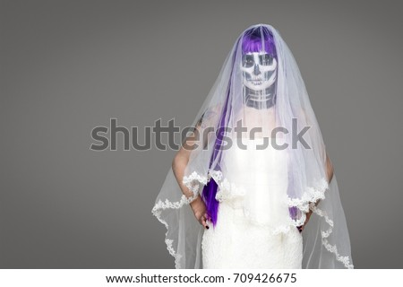 Portrait of woman looks at the camera with terrifying halloween skeleton makeup and purple wig bridal veil, wedding dress over gray background. Black wedding #709426675