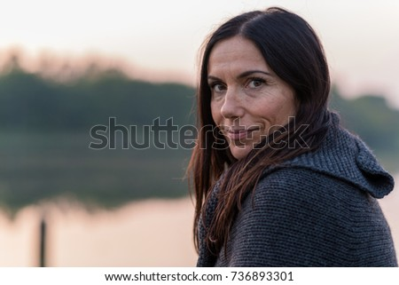 Portrait of woman outdoors in a public park during autumn sunset