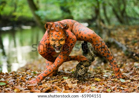 Portrait of woman pointed as leopard in a forest