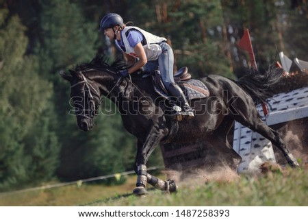 portrait of woman rider and black sport horse galloping energetically during eventing competition