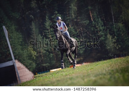 portrait of woman rider and black sport horse galloping energetically to obstacle for jumping during eventing competition