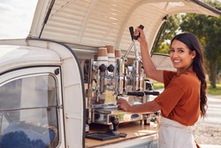 Portrait Of Woman Running Independent Mobile Coffee Shop Making Drink Standing Outdoors Next To Van