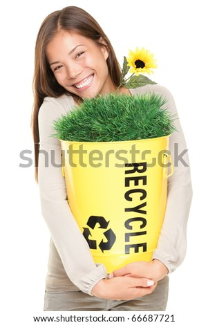 Portrait of woman showing recycle bin with grass and flower. Recycling concept. Young smiling asian / caucasian woman isolated on white background. - stock photo