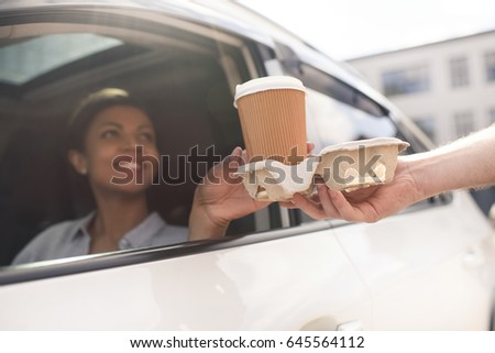 portrait of woman sitting in car and buying coffee to go