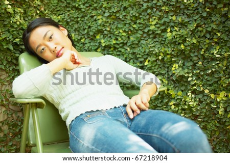 Portrait of woman sitting in chair outdoors