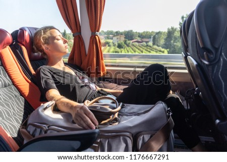 Portrait of woman sleeping on moving bus by window. Tired passenger sleeps on long countryside bus ride home.