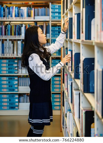 Portrait Of Woman Taking Book From Library Bookshelf Young Librarian Searching Books And One