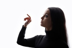 Portrait of woman touching the visual screen with her finger. White background. Young female in profile touches somethingin the air. Free space for text.