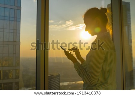 Portrait of woman using smartphone device against sunset cityscape view through window of skyscraper: scrolling and touching. Sun lens flare, golden hour. Leisure time, sightseeing, technology concept Foto d'archivio ©