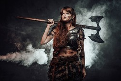 Portrait of woman viking wielding two handed axe and dressed in dark light armour in dark foggy background.