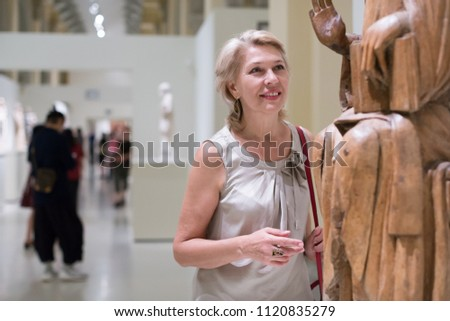 Portrait of woman visitor near sculpture in the historical museum