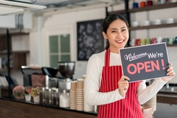 Portrait of woman waitress standing at her coffee shop gate with showing open signboard