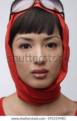 Portrait of woman wearing red sweater, scarf and sunglasses