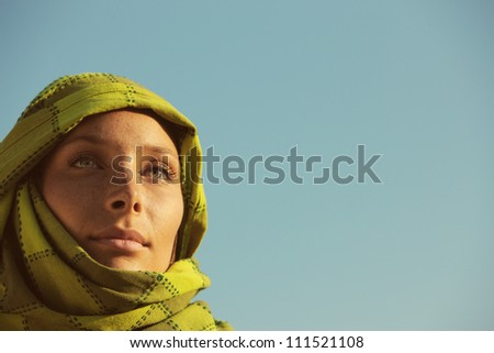 Portrait of woman with a green turban against blue sky, copy space