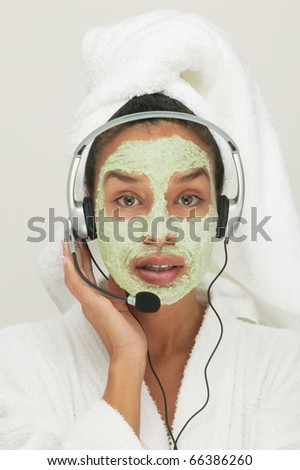 Portrait of woman with beauty mask on face listening to headphones