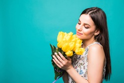 portrait of woman with bouquet of yellow tulips in hands isolated on green background