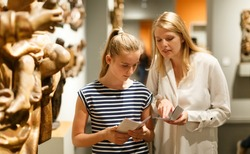 Portrait of woman with girl holding guidebook, standing in museum of ancient sculpture