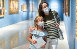 Portrait of woman with girl in medical masks standing in museum of art and looking at painting