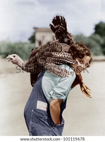 Portrait of woman with live turkey slung over shoulder